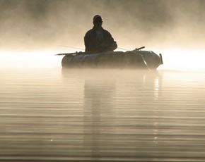 Angler in raft on a foggy lake.