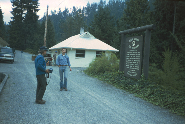 Hand stocking of high lakes is done with the support and oversight of the Washington Dept. of Fish & Wildlife (WDFW).  Here biologist Bob Pfeifer is walking toward the camera and volunteer Russ Tolsma, at the Tokul Creek Hatchery, prior to a high lake survey and stocking trip in the 1980s.