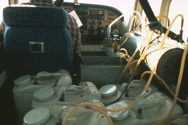 Here is an interior shot of the Cessna and the aerated containers ready for takeoff.  When the lake is reached, the container for that lake is dumped into the rectangular opening at the pilot's left elbow.