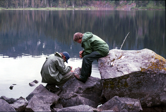 This slide shows two volunteers, John Thomas and Russ Tolsma, gathering data on fish stomach contents at an alpine lake.