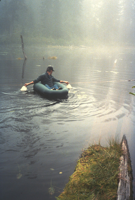 WDFW biologists gather data on high lakes personally, as time permits.  Here Bob Pfeifer sets out in his raft to measure the depth of a small pothole in the Middle Fork Snoqualmie River drainage.  This pothole was deemed too shallow to support fish.  Overall, about one-quarter to one-third of lakes are left fishless.