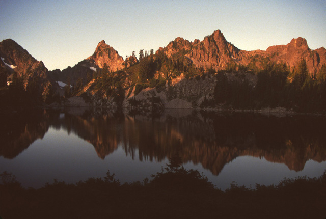 Here morning sunrise reflects of the peaks west of Gem Lake, north of Snoqualmie Pass.  Gem Lake is purposefully left fishless, in part due to the high level of hiking pressure this lake already receives due to the scenary.