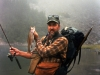 """Here I am on a fall daytrip with fishing gear in the fanny pack at my waist, day pack loaded with lunch and the ten essentials, camera case, rain pants and earth color shirt.  A nice 16"""" rainbow indicates success."""